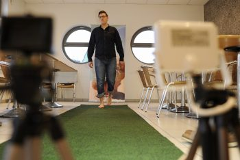 Ein Mann geht barfuß über einen grünen Teppich